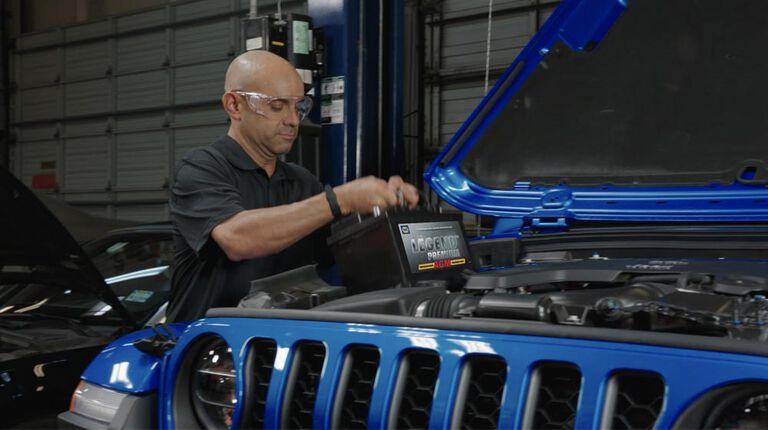 Kal Tire team member putting new battery in vehicle