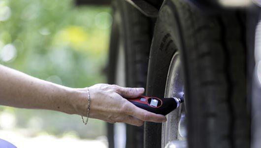 Checking tire pressure on a trailer tire